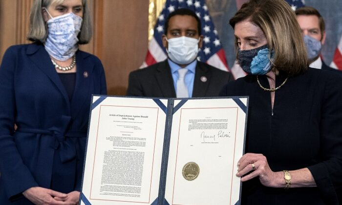 Speaker of the House Nancy Pelosi (D-Calif.) displays a signed article of impeachment against President Donald Trump at the U.S. Capitol in Washington on Jan. 13, 2021. (Stefani Reynolds/Getty Images) - bỏ phiếu luận tội TT Trump